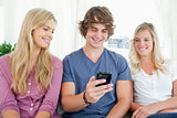 Three friends sitting and looking into the phone