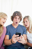 Shocked friends look at the man's phone
