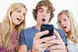 Three friends are surprised at the message on the phone