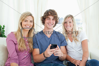 Three friends sitting together looking at the camera