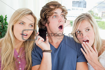 Three shocked friends listening to a phone conversation