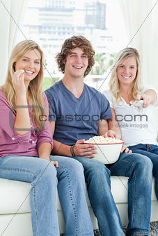 Three friends eating popcorn while smiling and about to change t