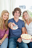 Three friends eating popcorn together as they look at the camera