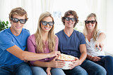 Friends smiling as they eat popcorn and watch a 3d movie