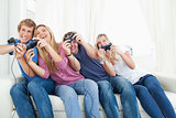 Friends enjoying video games as they all lean to the side
