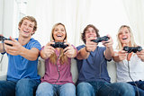 A group of friends all playing video games together and smiling