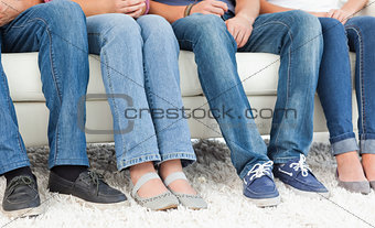 Four pairs of feet beside one another against the couch