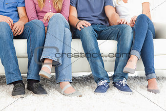 Four people sitting on the couch with the camera focused on the