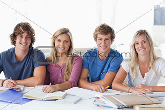 A smiling group of student sitting and looking at the camera