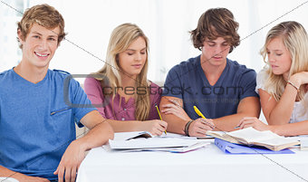 Four friends sitting at the table and studying