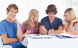 A group of students sitting together as they all study as one sm