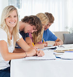 A smiling girl looks at the camera as her friends study