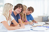 Students studying together with one man looking at the camera an