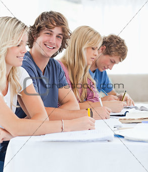Close up of a smiling student with friends looking at the camera