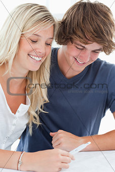 A smiling couple looking at the result of a pregnancy test