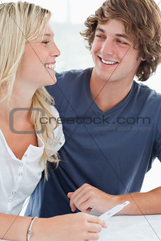 A smiling couple looking at one another as they hold a pregnancy