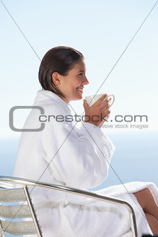 Side view of woman in bathrobe drinking coffee