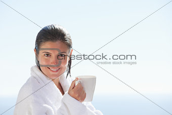 Smiling woman in bathrobe with a cup of coffee