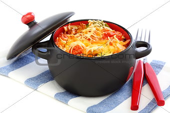 Black pan with sauteed vegetables and cheese.