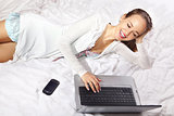 happy woman on the bed with laptop l
