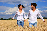 Happy couple running in a field smiling and holding hands