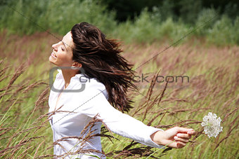 Beautiful woman outside, with wind in her face and a flower