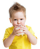 Funny angry kid drinking dairy product from glass isolated on wh