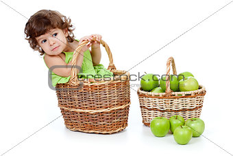 Adorable little girl with green apples in basket isolated studio