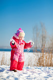child throwing snow in winter