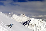 Snowboarder on off-piste slope in mountains