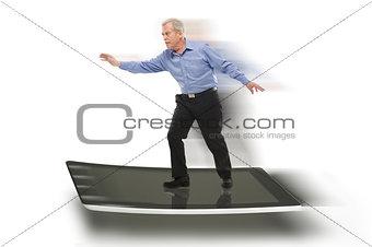 Senior businessman keeping balance on a PC tablet