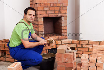 Masonry worker building fireplace
