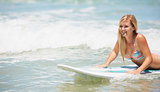 A pretty young blonde girl in a bikini lying on a surfboard