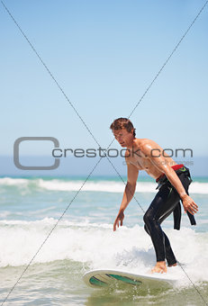 A young male surfer standing on his surfboard