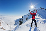 Mountaineer reaches the top of a snowy mountain in a sunny winter day.