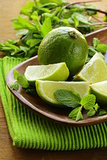 Fresh organic cut limes on wooden plate