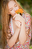 Village girl smelling flowers in nature