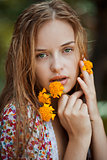Portrait of a blonde girl with green eyes holding yellow flowers