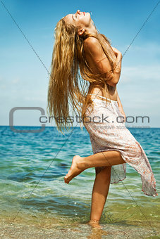 Glamour girl in a dress is awash in an ocean, Thailand