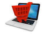 Red shopping trolley on laptop