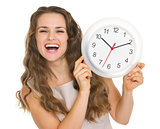 Happy young woman showing clock