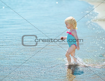 Baby girl walking into sea