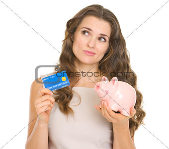 Thoughtful young woman holding credit card and piggy bank