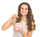 Happy young woman putting coin into piggy bank