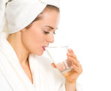Young woman in bathrobe drinking pure water