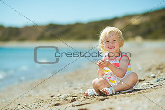 Happy baby girl playing on beach