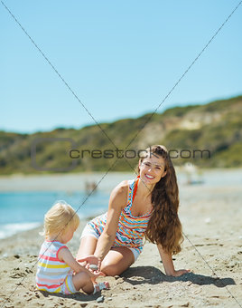 Happy mother and baby girl playing with sand on beach