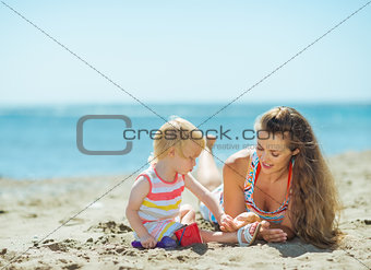 Mother and baby girl playing with sand on beach