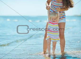 Mother and baby girl playing at seaside