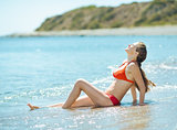 Happy young woman in swim suite laying on sea shore